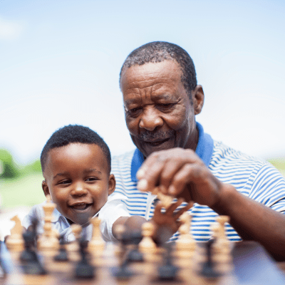 A grandfather plays chess with his grandson at Milestone Retirement Communities