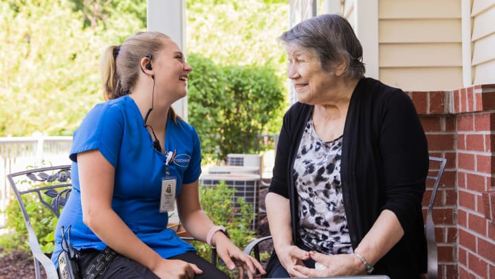 Image of a Touchmark caregiver and resident laughing together.