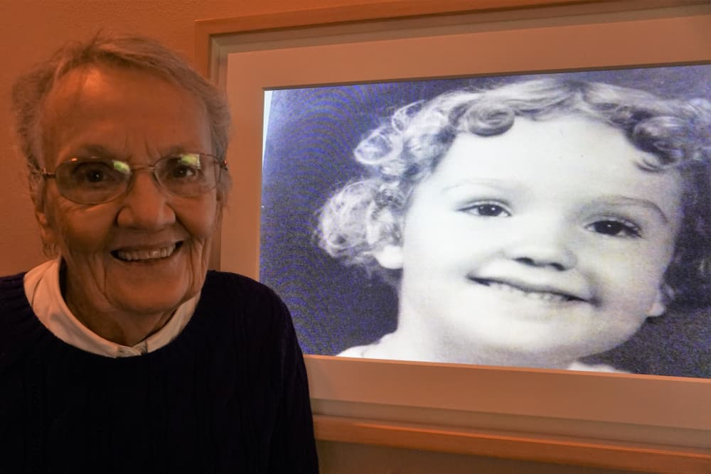 Resident smiling in front of childhood photo on Meural Canvas at our senior living community