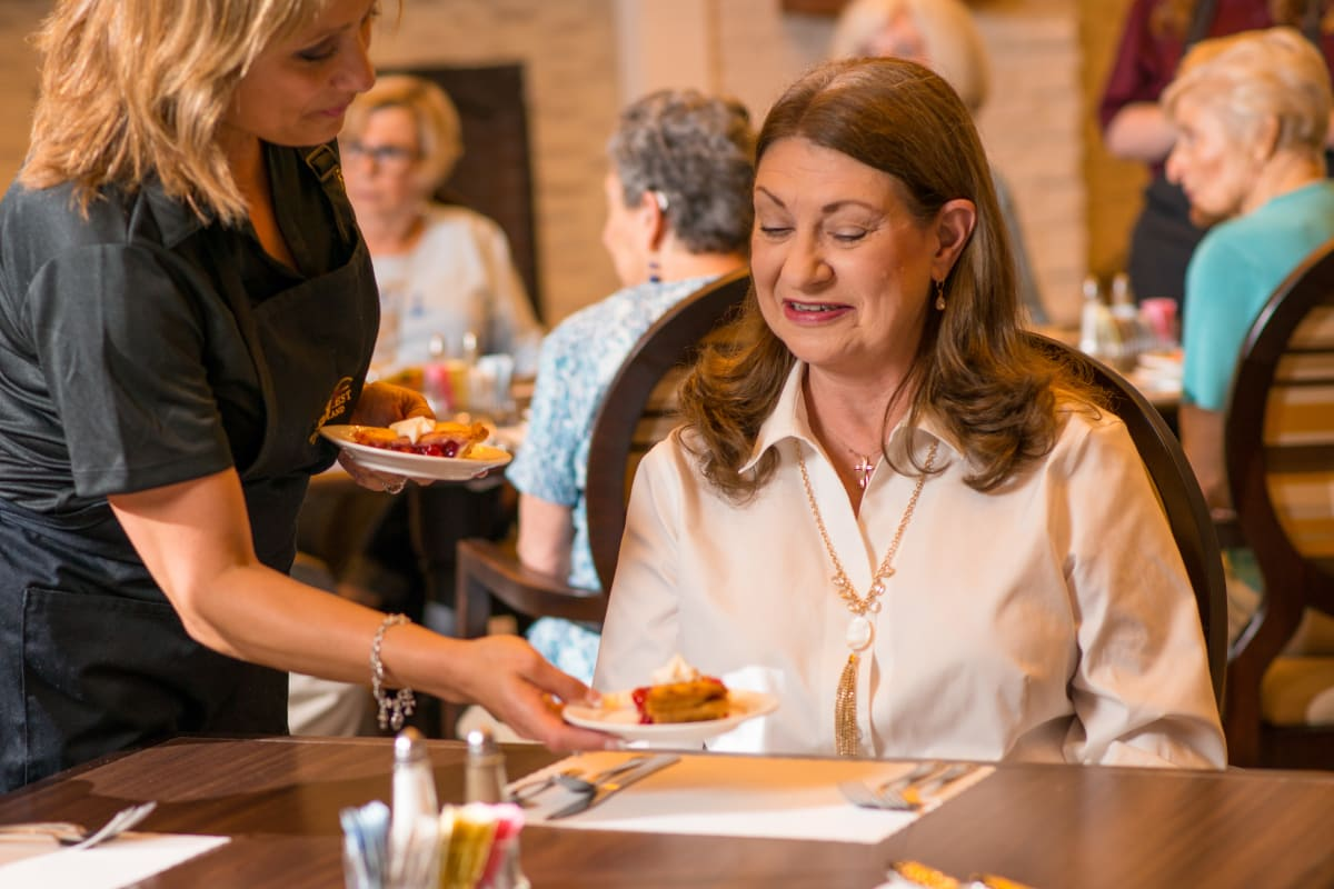 Resident choosing from a menu at Landing at Watercrest Shadow Creek Ranch in Pearland, Texas