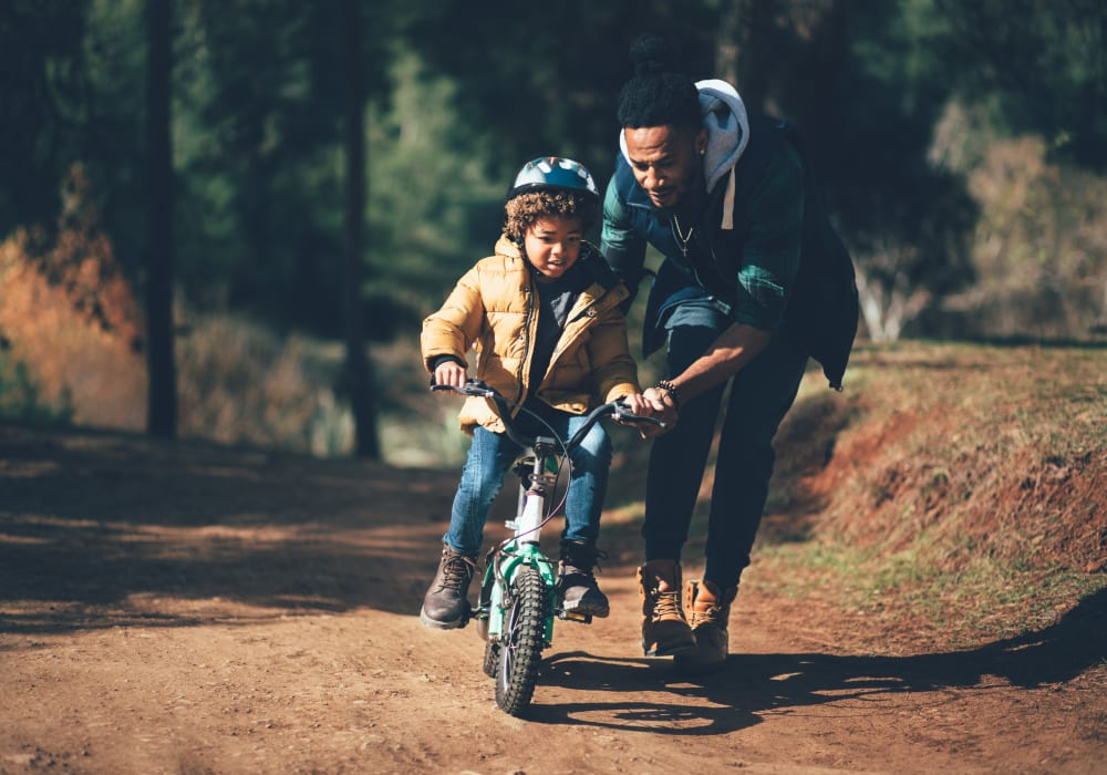 Father teaching his son how to ride a bike near The Trails at Canyon Crest in Riverside, California