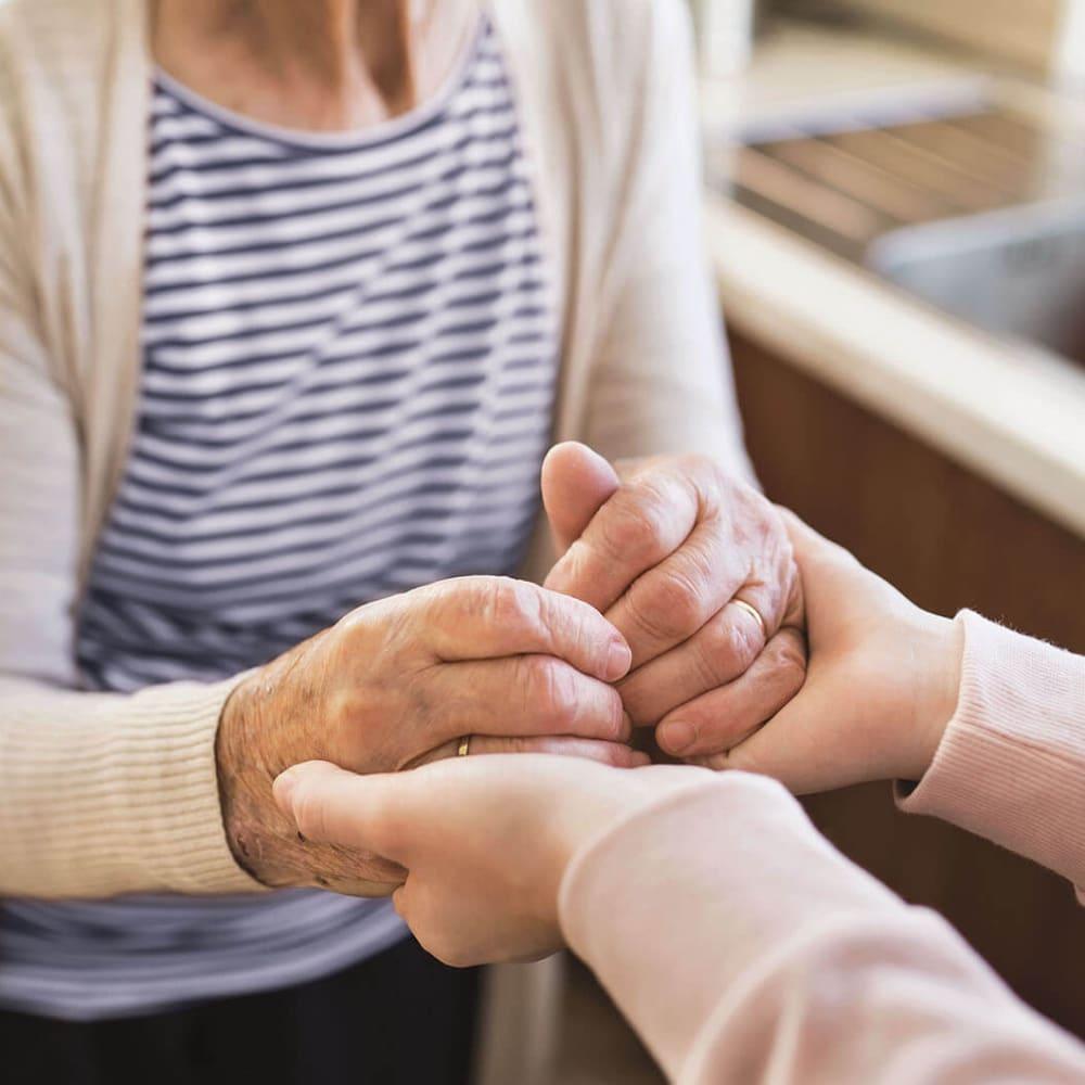Resident holding hands with her caretaker at Anthology of South Jordan in South Jordan, Utah