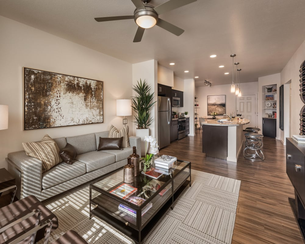 Luxuriously furnished open-concept living area with hardwood floors in a model home at Vistara at SanTan Village in Gilbert, Arizona