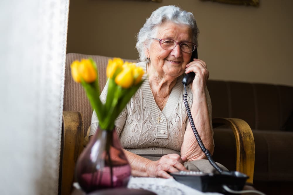 A residents talking on the phone at Merrill Gardens at Columbia in Columbia, South Carolina.