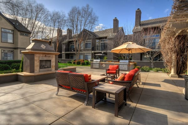 A community patio with comfortable seating and umbrellas for shade at Larkspur Woods in Sacramento, California