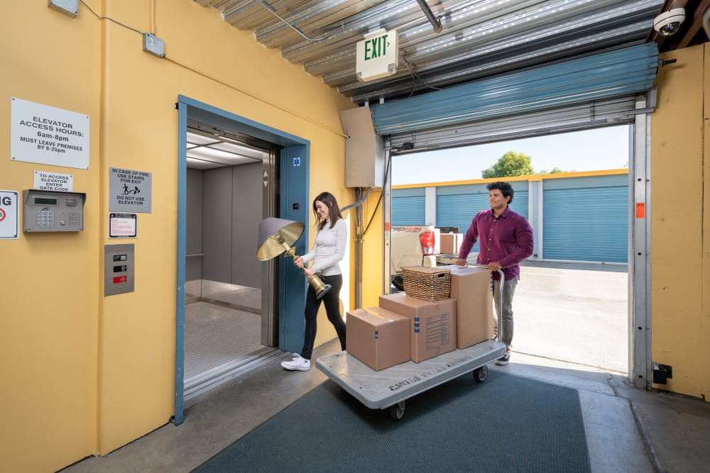 Couple with moving dolly walking into Castro Valley Storage LLC in Castro Valley, California