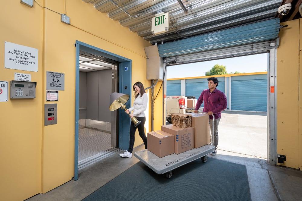 Couple with moving dolly walking into Hayward Storage LLC in Hayward, California