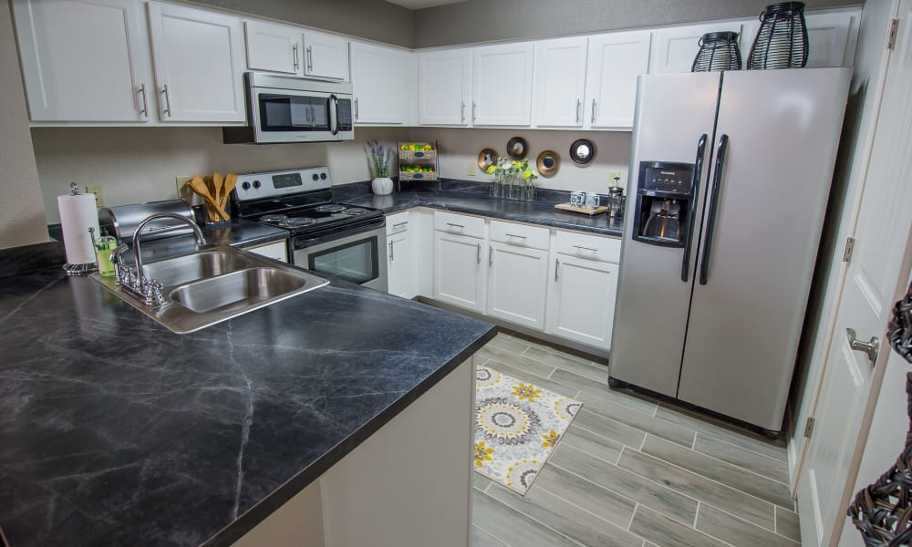Bright kitchen with black granite counters at Cottages at Tallgrass Point Apartments in Owasso, Oklahoma
