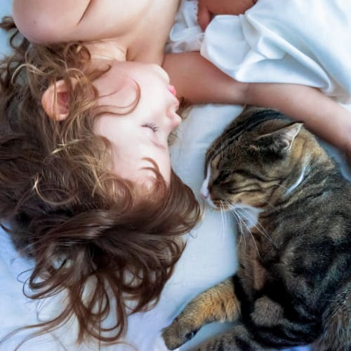 Happy resident child and her cat relaxing in their new home at Cadia Crossing in Gilbert, Arizona