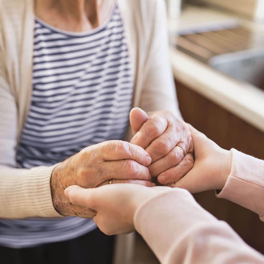 Caretaker holding hands with a senior resident at Anthology of Olathe in Olathe, Kansas