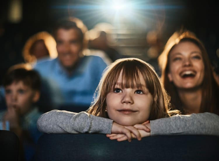 Family enjoying a movie at a cinema near Stone Creek at The Woodlands in The Woodlands, Texas