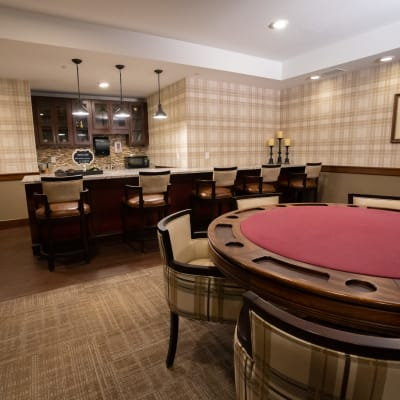 Game room with card table and bar at The Sanctuary at St. Cloud in St. Cloud, Minnesota