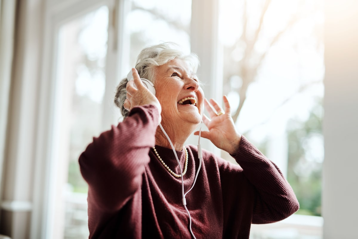 Resident enjoying listening to music at The Meridian at Boca Raton in Boca Raton, Florida