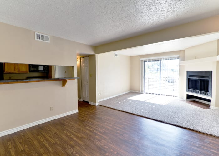 Hardwood floors, plush carpet, and a fireplace in model home's living area at The Belmont in Grand Prairie, Texas