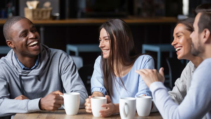 Group of people sitting around a table smiling and holding coffee mugs.