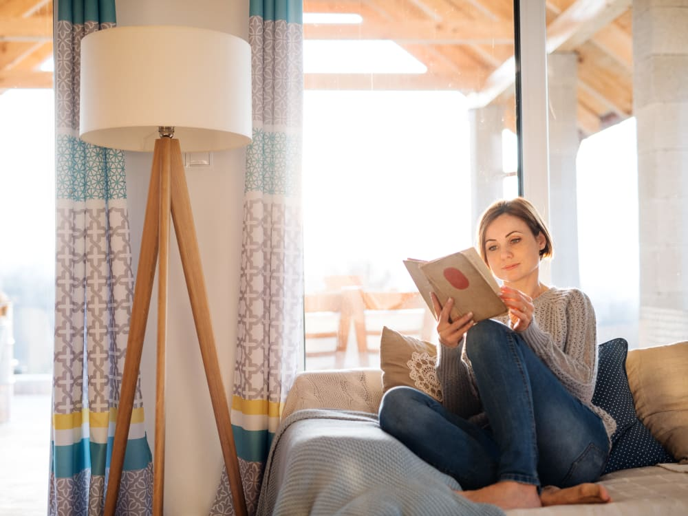 Resident reading a book on couch near window at Haven Apartment Homes in Kent, Washington