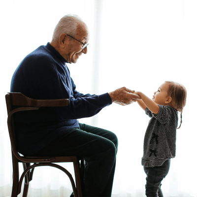 A grandparent holds hands with his granddaughter at Milestone Retirement Communities