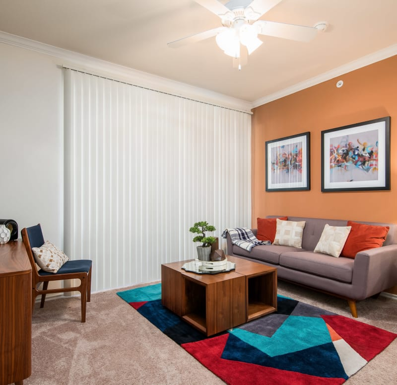 Retro-furnished living area with plush carpeting and a ceiling fan in a model home at Rockbrook Creek in Lewisville, Texas