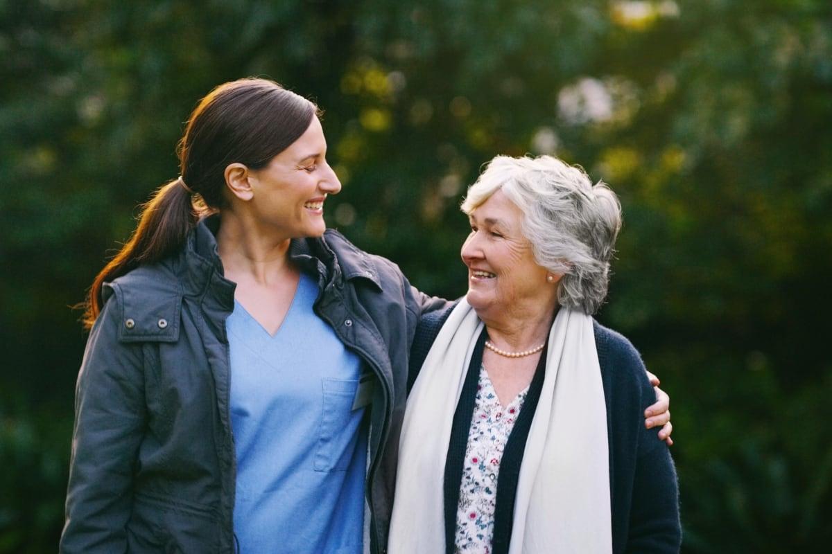 Resident walking with caregiver at Monark Grove Clarkston in Clarkston, Michigan
