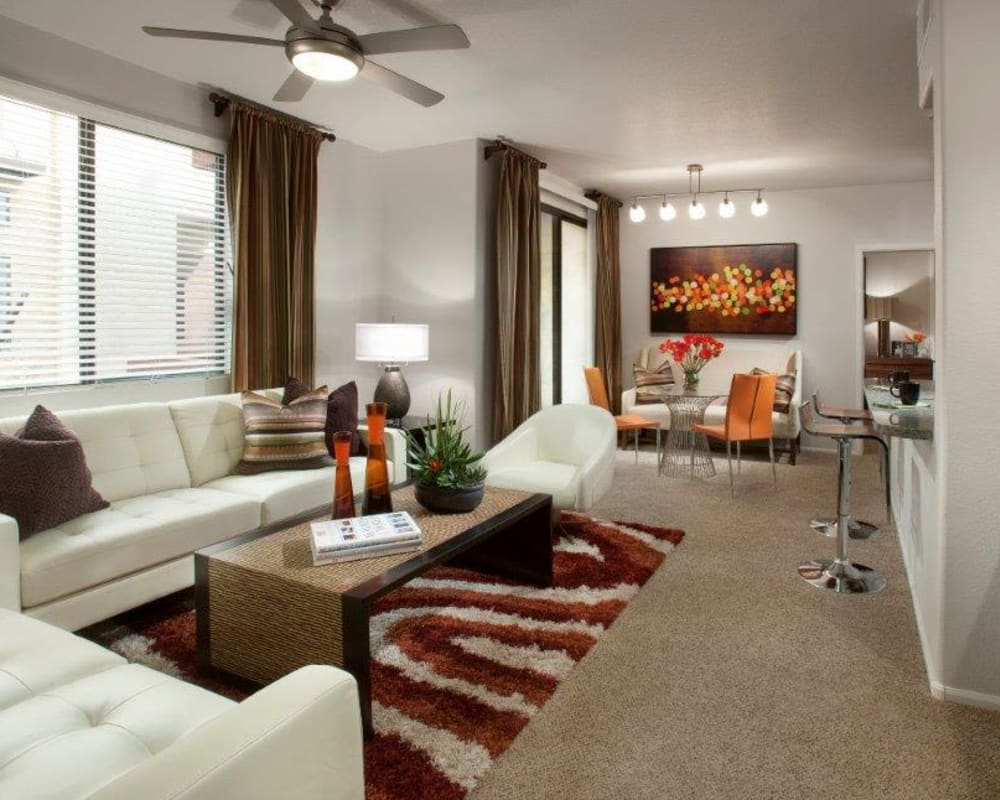 Large, well-furnished open-concept living area with plush carpeting in a model home at Vive in Chandler, Arizona
