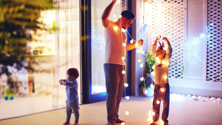 Father and sons decorate their patio with Christmas lights