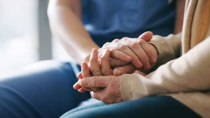 Resident holding hands with a caretaker at Quail Park of Lynnwood in Lynnwood, Washington