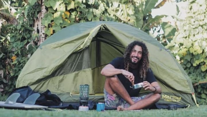 A man named Dr. Cliff K. camping with a tent in the background