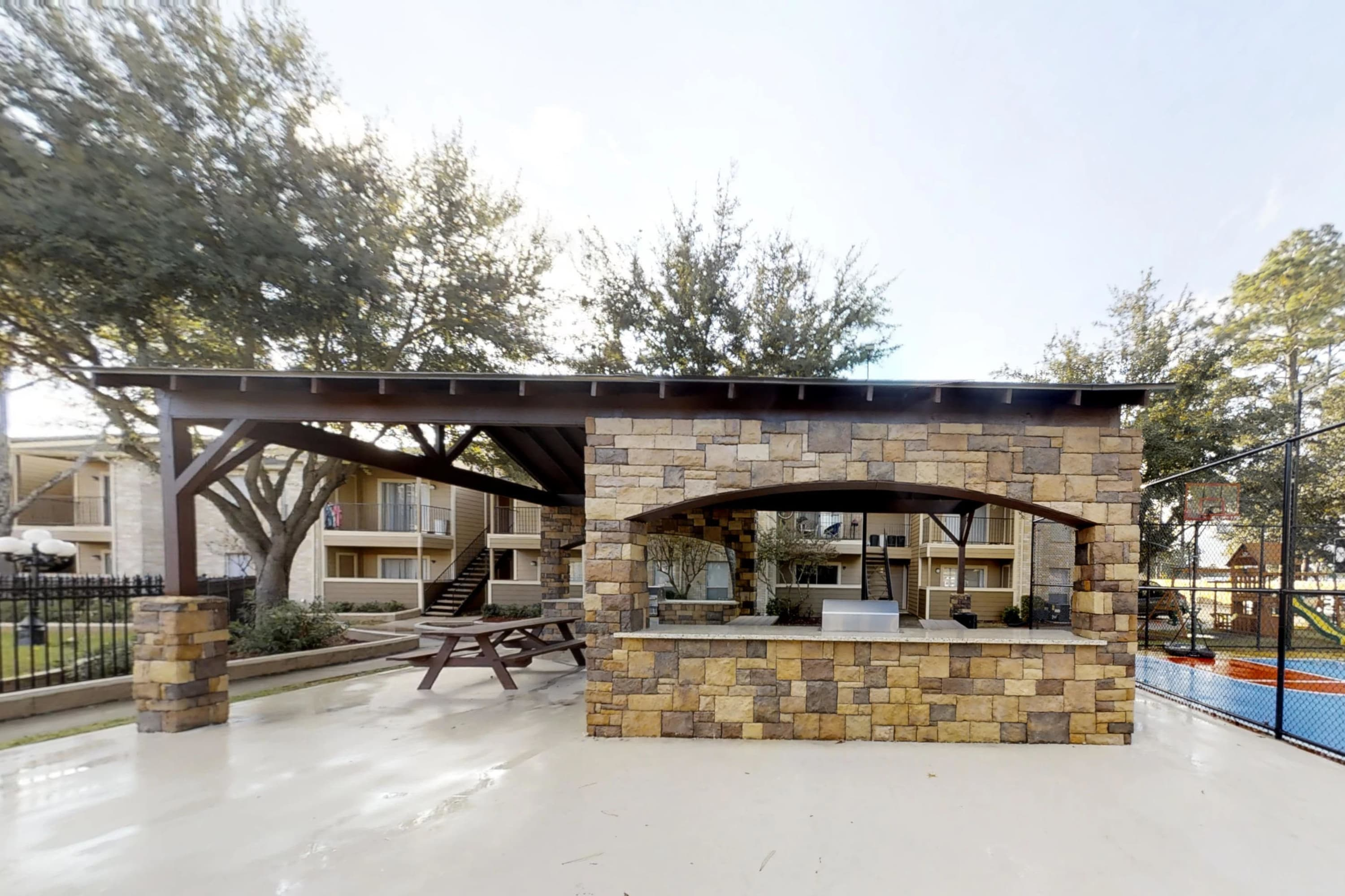 Outdoor kitchen next to pool great for entertaining at apartments in Humble, Texas