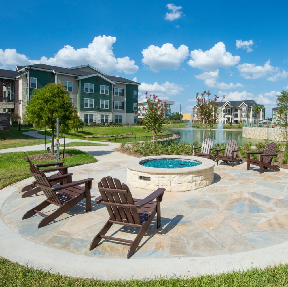 Outdoor lounge area with gas-fueled fire pits at Elite 99 West in Katy, Texas