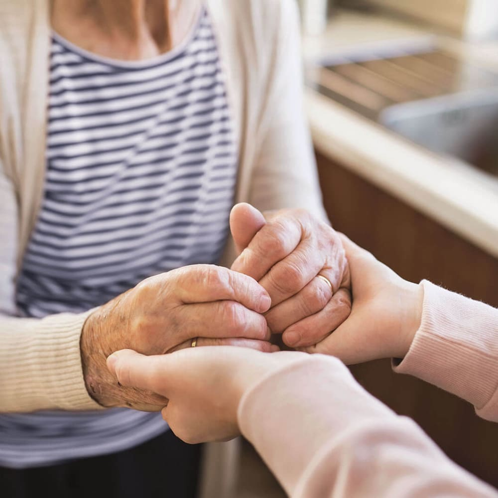 Caretaker and resident holding hands at Anthology of Overland Park in Overland Park, Kansas