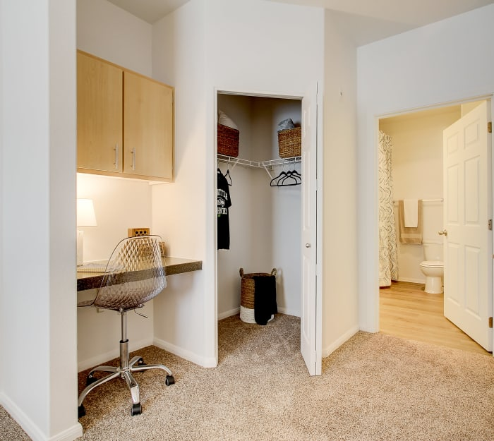 Study nook, walk-in closet, and en suite bathroom in the master bedroom of a model home at River Trail Apartments in Puyallup, Washington