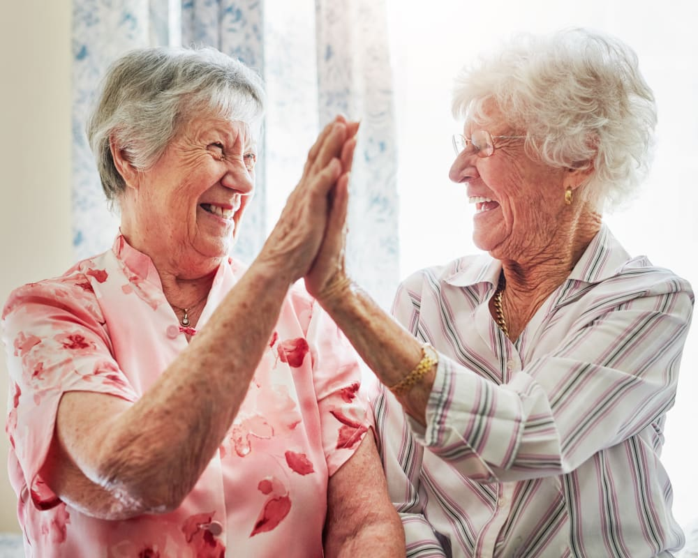 Two residents smiling and giving each other a high-five at Milestone Senior Living in Stoughton, Wisconsin.