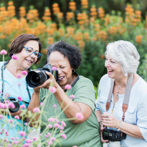 Resident taking a picture of some flowers with a large camera at Sunstone Village in Denton, Texas