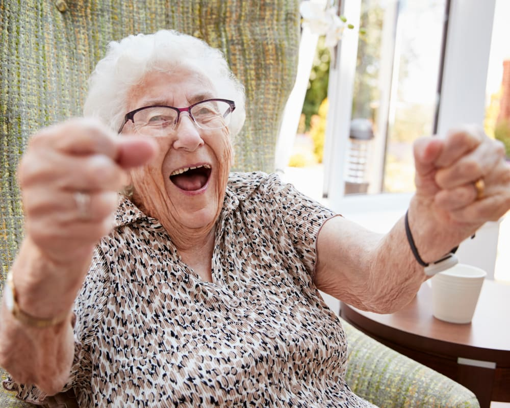Resident in a chair reaching upwards and smiling at Edencrest at Siena Hills in Ankeny, Iowa.