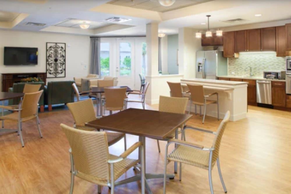 An open kitchen and dining room seating at Ortega Gardens Alzheimer's Special Care Center in Jacksonville, Florida