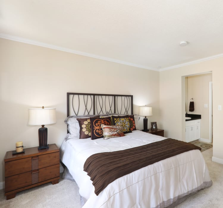 Master bedroom with plush carpeting and an en suite bathroom in a model home at Sofi Redwood Park in Redwood City, California