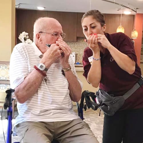 Resident and team member playing music at The Oxford Grand Assisted Living & Memory Care in McKinney, Texas