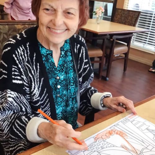 A resident smiling and coloring at Oxford Glen Memory Care at Grand Prairie in Grand Prairie, Texas