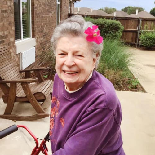 Resident smiling with a flower in her hair at Oxford Glen Memory Care at Grand Prairie in Grand Prairie, Texas