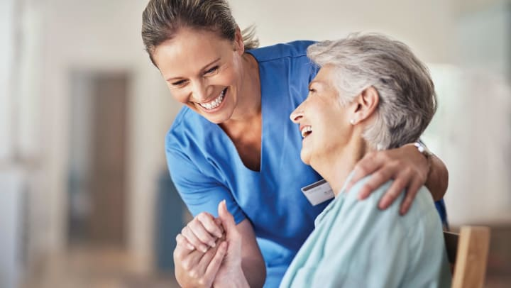 Woman and nurse holding hands and smiling