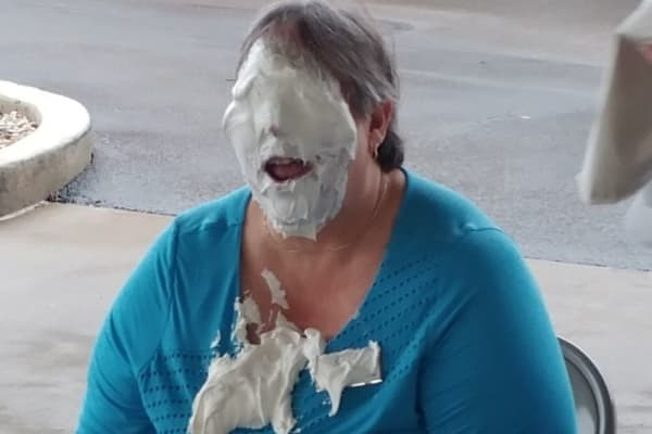 Staff member with a face full of pie for an Alzheimer's fundraiser at Discovery Senior Living in Bonita Springs, Florida