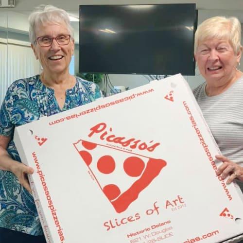 Residents holding pizza at Oxford Villa Active Senior Apartments in Wichita, Kansas