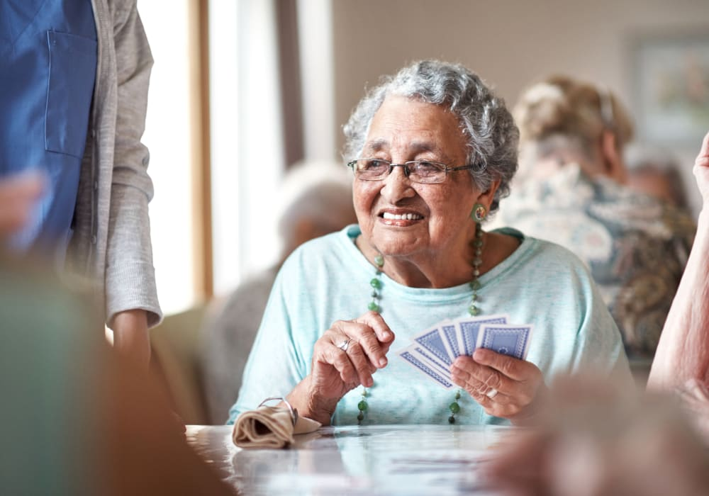 Resident playing cards at Autumn Grove Cottage at Pearland in Manvel, Texas