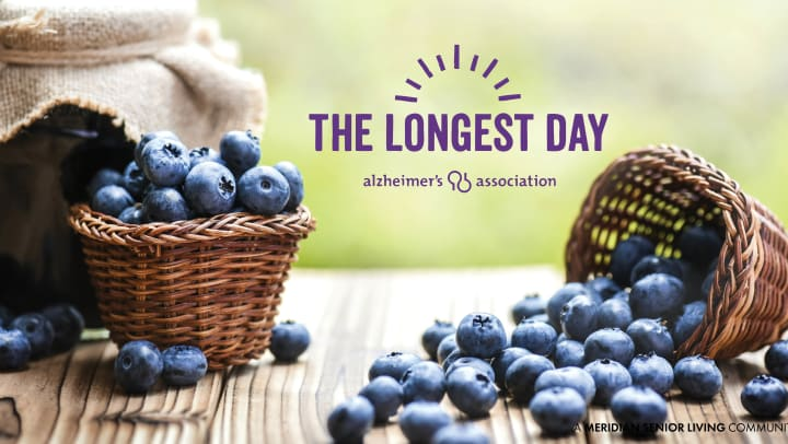 Blueberries falling out of a basket and on a table. The Longest Day purple logo in background.