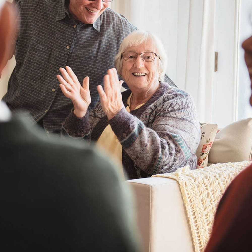 Happy resident clapping at Anthology of Farmington Hills in Farmington Hills, Michigan
