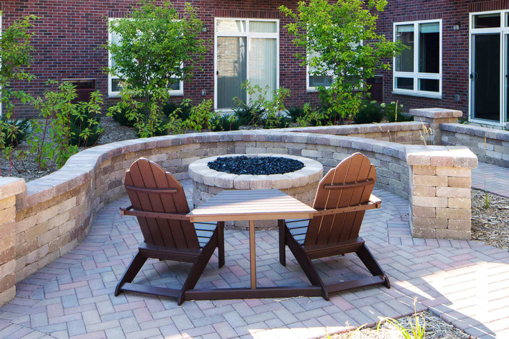 Outdoor fireplace with seating at Remington Cove Apartments in Apple Valley, Minnesota