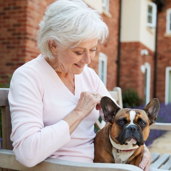 Senior woman sitting outside with her dog at Quail Park at Shannon Ranch in Visalia, California