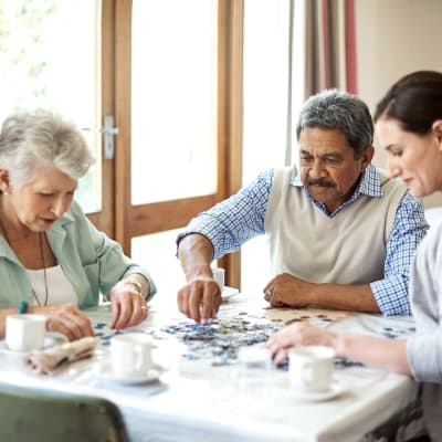 A family putting a puzzle together at Wellsprings Assisted Living in Ontario, Oregon