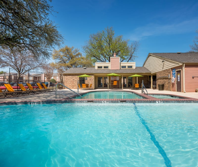 Large swimming pool with a sundeck at The Fairway Apartments in Plano, Texas