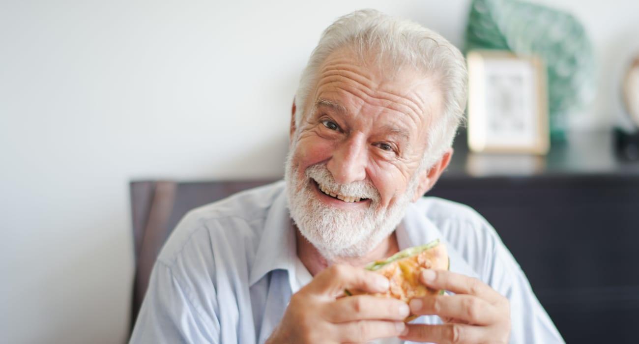 Resident enjoying a burger at Merrill Gardens at Oceanside in Oceanside, California.